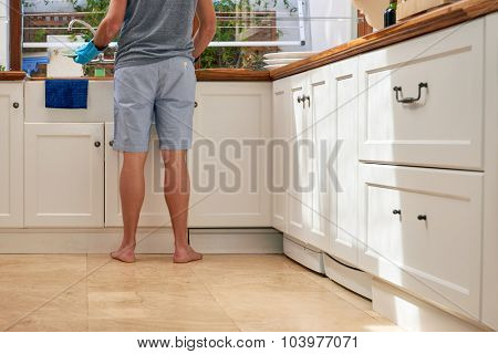 Rear low angle view of male in the kitchen doing household chores