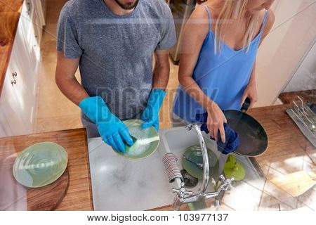 Over view of couple doing household chores in the kitchen