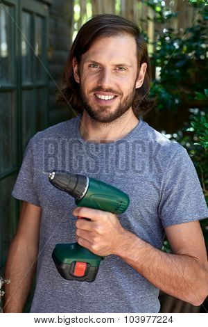 Portrait of confident handyman holding a drill in hand