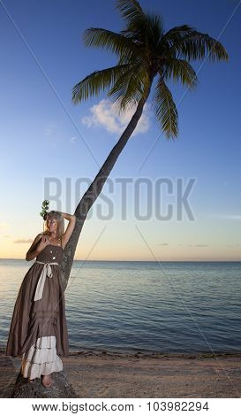 The beautiful woman with a rose at a palm tree. Tahiti