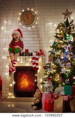 Smiling funny child in Santa red hat holding Christmas gift in hand.