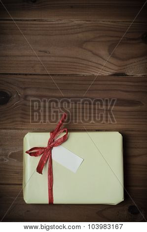 Wrapped Gift Package With Red Raffia Bow On Wood Planking - Retro Style