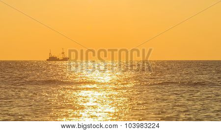 Trawler fishing at sea at sunset in autumn