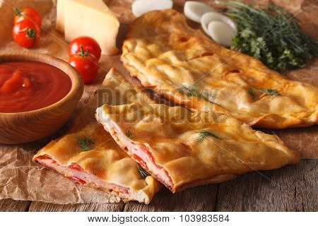 Cut Italian Pizza Calzone With Ham Closeup And Ingredients. Horizontal