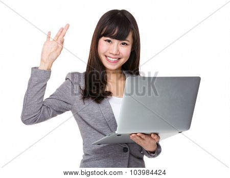 Businesswoman use of the notebook computer and ok sign gesture