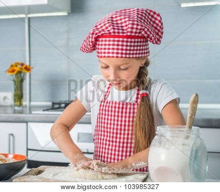 cute little girl kneading a dough on a kitchen