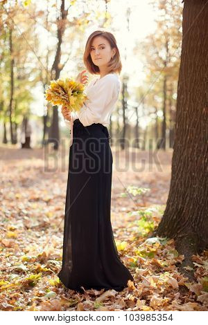 portrait of elegant slim young girl in autumn park