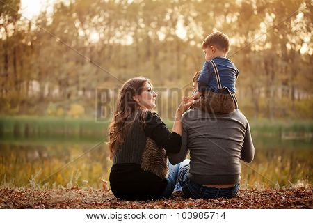 family on the banks of the river in the fall