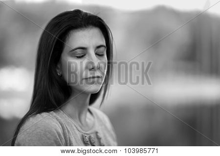Pretty woman with eyes closed black and white portrait