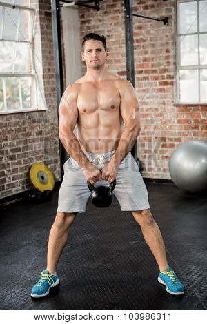 Portrait of shirtless man lifting kettlebell at the gym