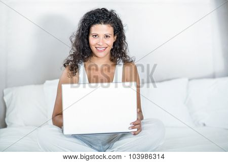 Portrait of beautiful pregnant woman using laptop while sitting on bed at home
