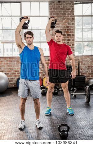 Portrait of muscular men lifting kettlebell at the gym
