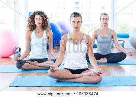 Women doing lotus pose in fitness studio