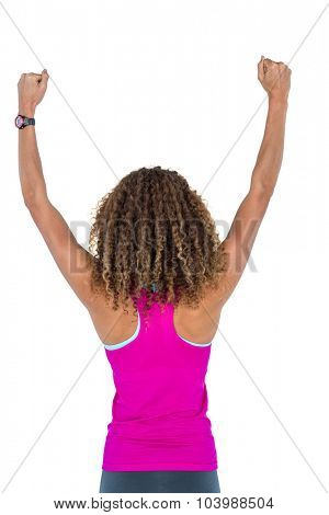 Rear view of woman cheering with arms raised against white background