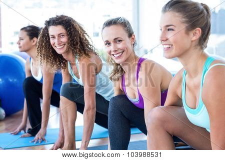 Portrait of women doing high lunge pose on exercise mat in fitness studio