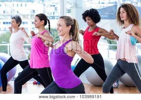 Women exercising with clasped hands and stretching in fitness studio