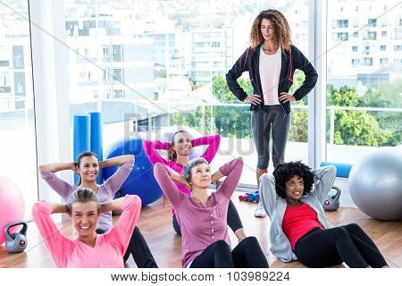Young female trainer assisting women sit ups at gym