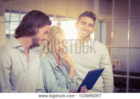 Portrait of smiling businessman standing with colleagues in creative office