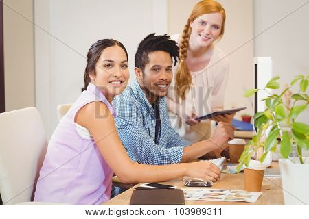 Portrait of smiling business people working together at desk in office
