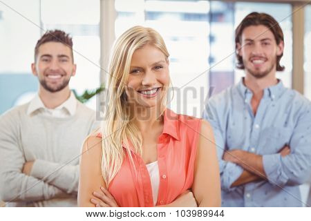 Portrait of smiling businesswoman standing with arms crossed with male colleagues at meeting room in creative office
