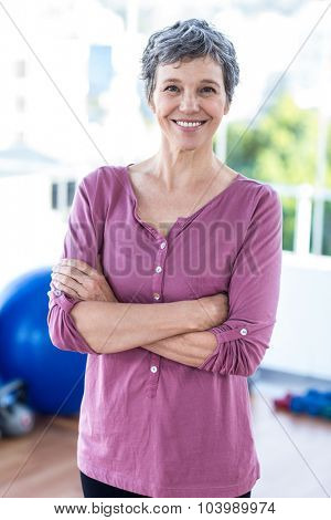 Portrait of smiling matured woman standing in fitness studio