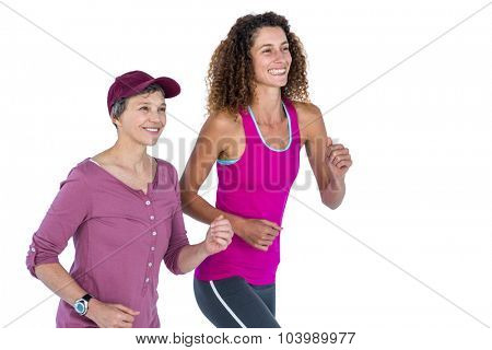 Cheerful female friends jogging against white background