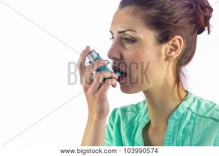 Woman looking away while using asthma inhaler against white background