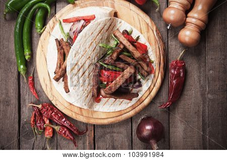 Fajitas, mexican beef stripes with vegetables in tortilla wrap