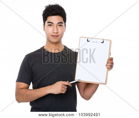 Young man with pen point to clipboard