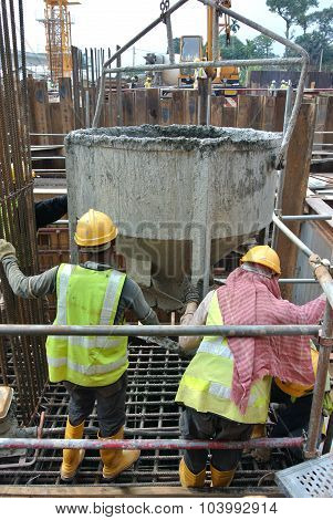 A group of construction workers pouring concrete into pile cap formwork