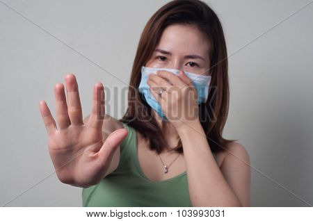 Asian woman in a green shirt wearing a mask showing stop symbol Focus hand.