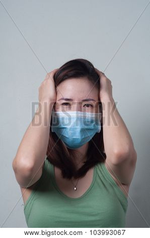Asian woman in a green shirt wearing a mask and headaches.