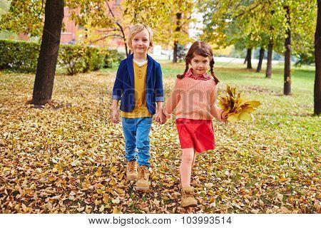 Little friends walking down yellow fallen leaves in park