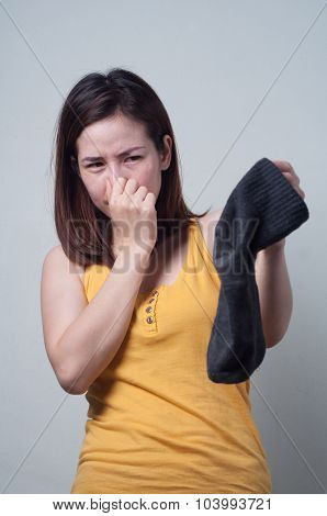 Portrait Of Asian Woman In A Yellow Dress Smelling Socks Foul.