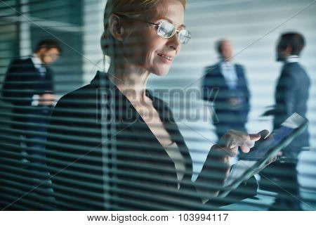 Mature employee using touchpad in working environment