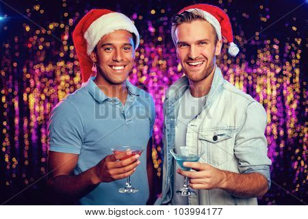 Two happy Santa guys with cocktails looking at camera at party
