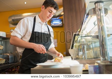 Low angle view of male worker cutting sandwich at display cabinet in bakery