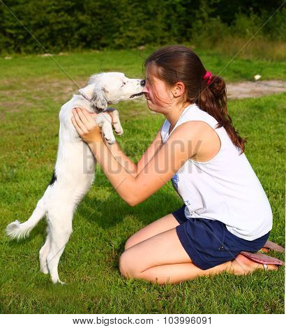 Girl With White Puppy On The Summer Backgroune