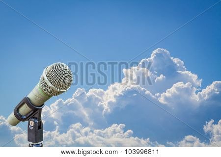 Microphone On A Stand Over Blurred Cloudy Blue Sky
