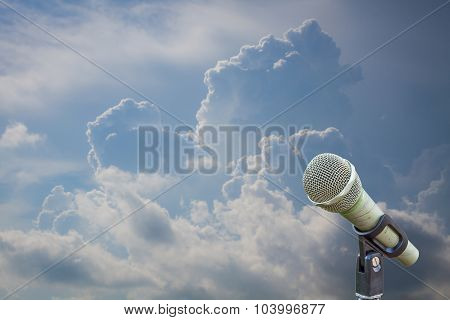 Microphone On A Stand With Blurred Dark Blue Stormy Clouds. Dramatic Storm Cloudscape