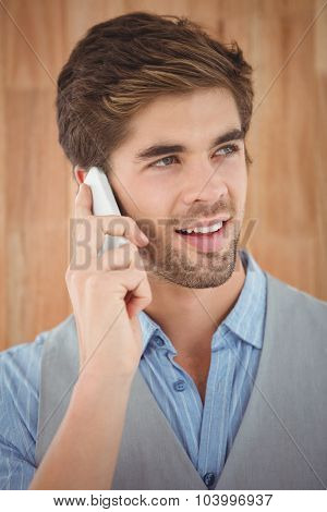 Close-up of hipster talking on mobile phone while standing against wooden wall