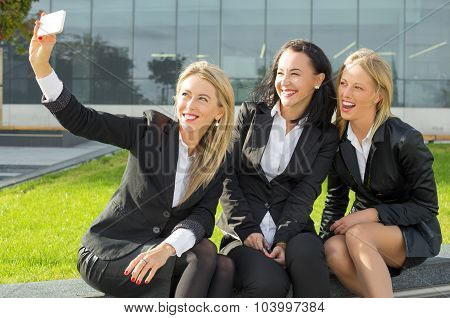 Three women in suits taking a photo