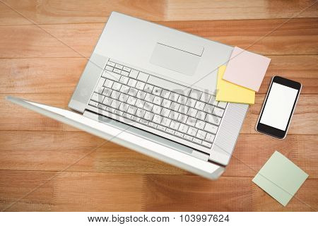 High angle view of laptop with sticky notes and smartphone at desk