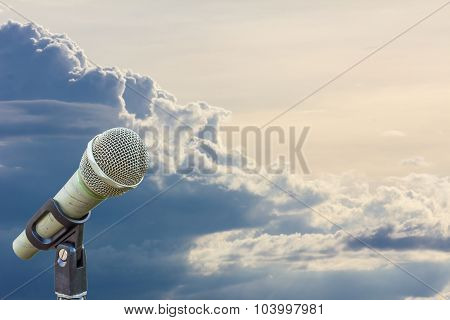 Microphone On A Stand With Blurred Gray Big Cloud Before Raining In The Evening, Copyspace On The Ri