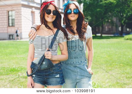 Portrait of two happy twins sisters stay together wearing bright bandanas, best fiend enjoy amazing time together.