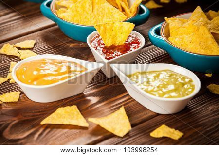 Plate of nachos with salsa, cheese and guacamole dips