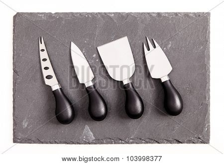 Rough textured slate board with cheese knives on white background