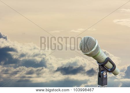 Microphone On A Stand With Blurred Gray Big Cloud Before Raining In The Evening, With Copyspace.