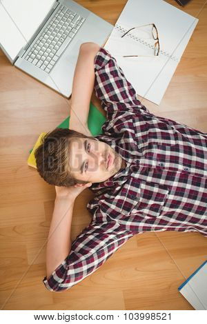 Portrait of hipster with hands behind head lying on hardwood floor