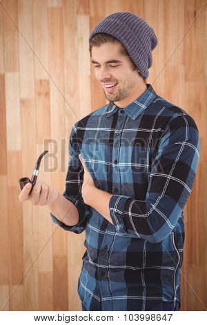 Happy hipster holding smoking pipe while standing against wooden wall in office